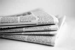 black and white image of stack of newspapers
