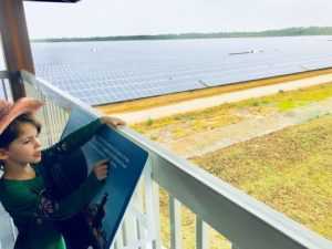 Kid is looking at fields of solar panels